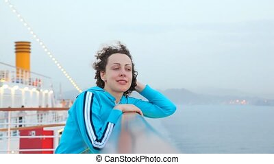 woman stand on deck of cruise ship - smiling young woman...