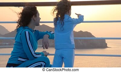 woman with her daughter looks at sunset