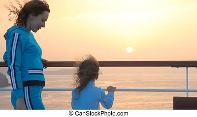mother and daughter on ship looks at sunset