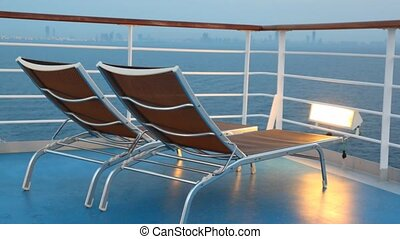 pair of deck chairs on moving cruise ship in night sea near...