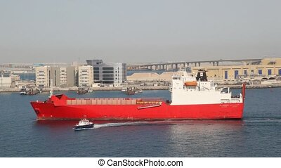 moving barge and cutter on water against city in Abu Dhabi,...
