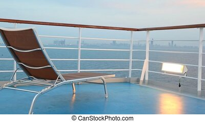 deck chair on moving cruise ship in night sea near city