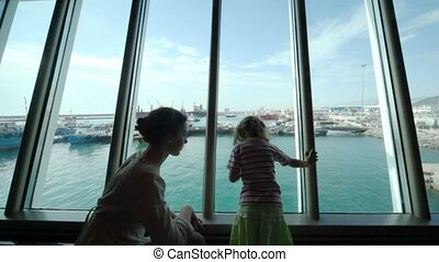 mother with daughter looks at ship in sea port