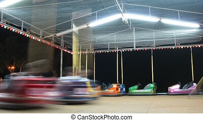 Children go for a drive on machines in fairground attraction.