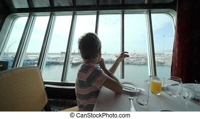 boy having breakfast in cruise ship in port