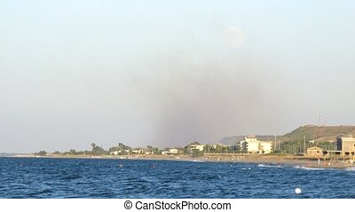 Italian settlement on coast, a smoke over settlement.