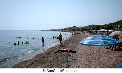 People on a beach in sunny day in Rome, Italy. - ROME - JULY...