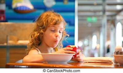 little girl eats in cafe on cruise ship