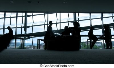 Silhouettes of people opposite to windows in airport Time...