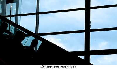 Silhouettes of the people moving on the escalator against a window.