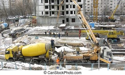 Work on a building site: workers, the crane, cement mixer in Moscow, Russia.