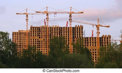 Under construction houses and cranes against sunset sky in...