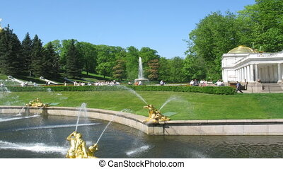 tourists in a beautiful garden of a Petergof with fountains