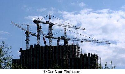 Under construction houses and cranes against sky in Moscow,...