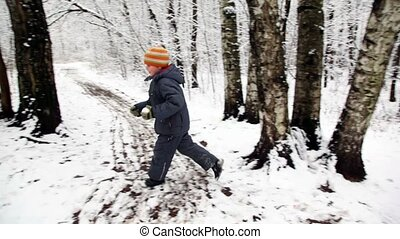 Boy with snowball runs round in snow forest - Boy in orange...