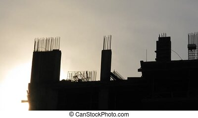 Silhouette of under construction house against sky and...