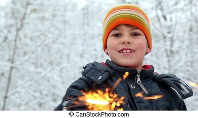 Boy with Bengal fire in snow forest - Boy in orange hat with...