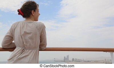 woman stands on deck and looks at city