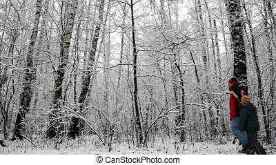 Father and the son walk in snow forest
