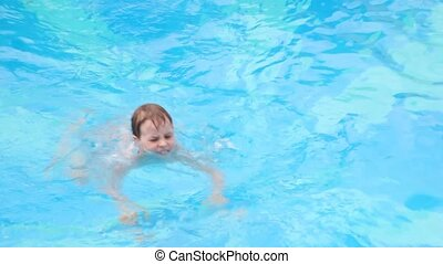 boy swimming in open-air water pool