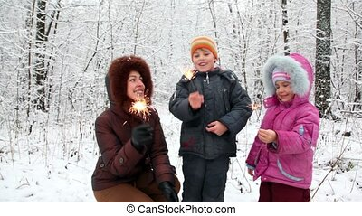 Mother with boy and girl with Bengal fires in snow forest -...