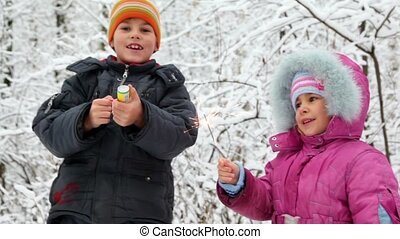 Boy with petard and the girl with Bengal fire in snow forest