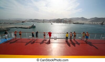 tourists stands on deck of ship and looks at seaport,...