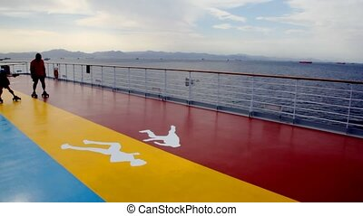tourists rides on roller skates on deck of cruise ship