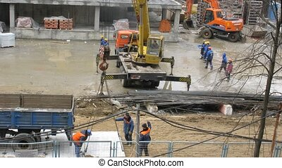 Work on a building site: workers, the crane, plates in Moscow, Russia.