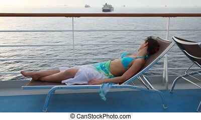 woman lying on deckchair on deck of cruise liner