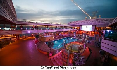 Open-air water pool on deck of cruiser in night in Persian...