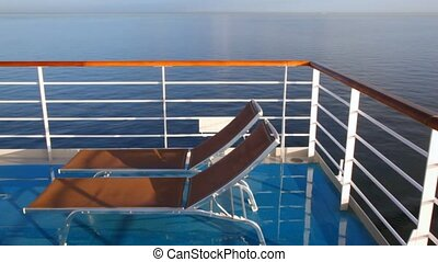 pair of deckchairs on deck of cruise liner moving in sea