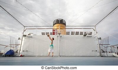woman plays basketball on open-air playground - young woman...