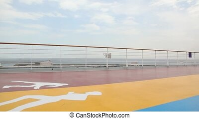 aged couple walks on deck of cruise ship in sea