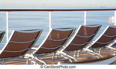deckchairs on deck of cruise ship moving on water against...