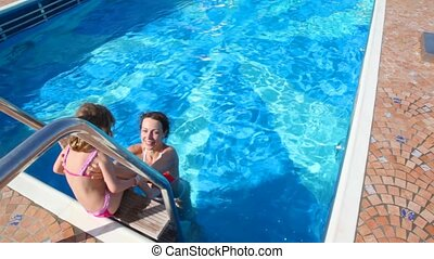 woman and girl having fun in swimming pool - happy woman and...