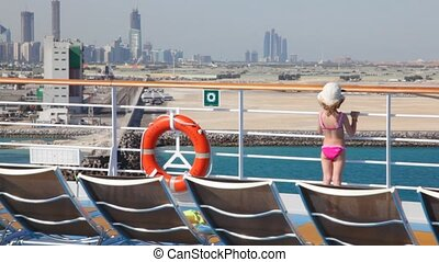 girl stands on deck of cruise liner