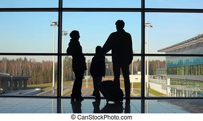 silhouettes of family standing against window in building