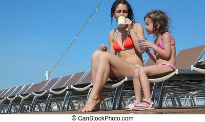 mother and daughter sits on deckchairs on deck of cruise...