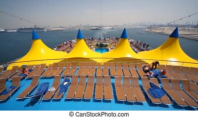 top deck of cruise ship moving out from moorage of Dubai