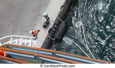 workers unbends mooring line of cruise ship from moorage -...