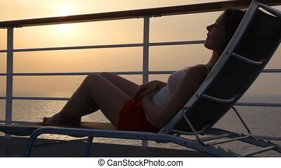 woman lying on deckchair on deck of cruise ship in evening...