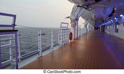 deck with illumination of cruise liner in evening sea