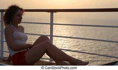 woman lying on deckchair on deck of cruise liner - happy...