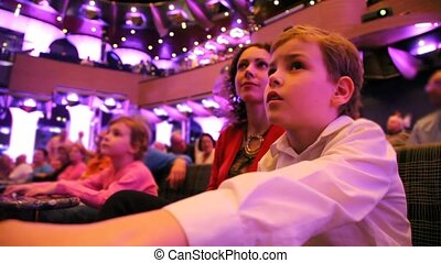 mother with son and daughter sits on spectator's seats in...