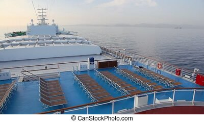 rows of deckchairs on top deck of cruise ship