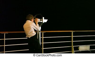 boy looks at sea through binocular - boy looks at night sea...