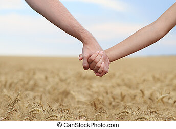 Young couple holding hands in the field Close-up