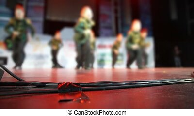 focus on wires of audio equipment on floor of stage during dance routine