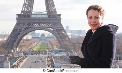 woman stands against Eiffel Tower in Paris - happy woman...
